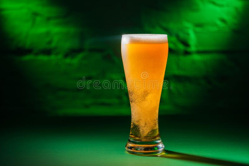 Close-up view of glass with beer in green light, saint patricks. Day concept royalty free stock images