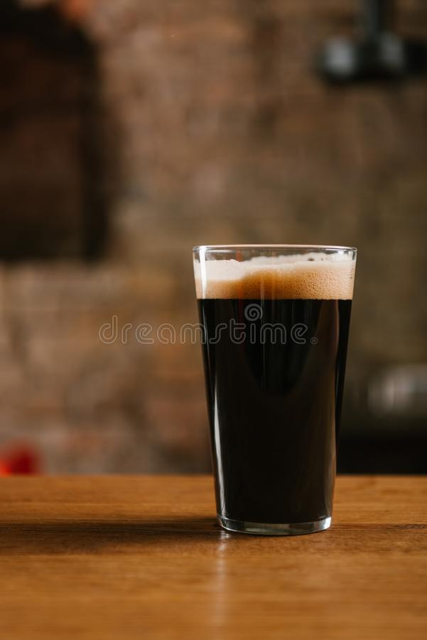 Close-up view of glass with delicious dark beer on table in pub royalty free stock images