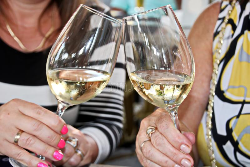 Close-up view of glasses of cold wine in the hands of the women sitting at the table of a summer cafe. royalty free stock photo