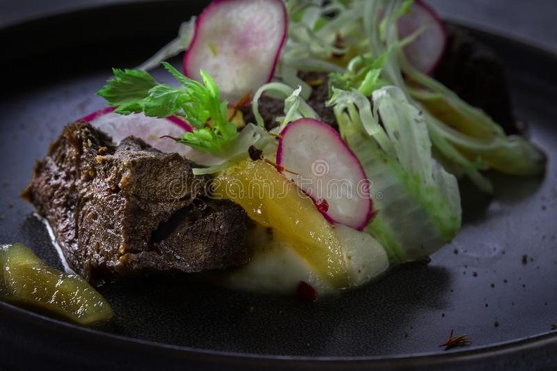 Close up view on Glazed Beef Cheek with celery puree and ginger pear on gray background in restaurant stock images