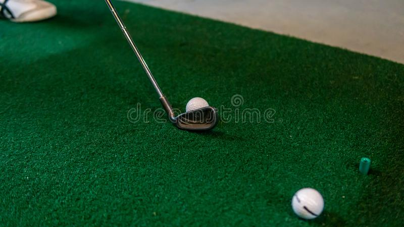 Close up view of the golf club at the ball on the green carpet mat at the driving range royalty free stock images