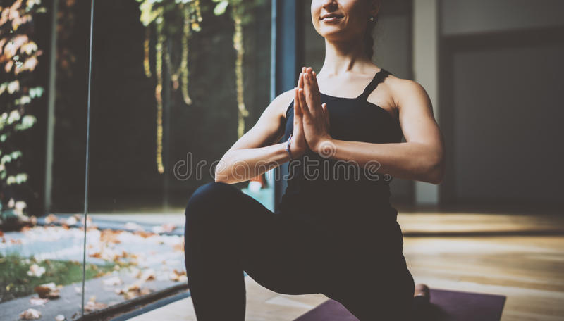 Close up view of gorgeous young woman practicing yoga indoor. Beautiful girl practice ardha matsyendrasana in class royalty free stock images