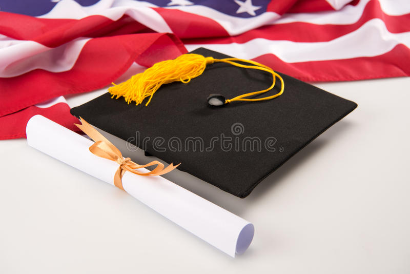 Close-up view of graduation mortarboard, diploma and us flag on grey stock photography