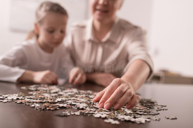 close-up view of grandmother and granddaughter playing with jigsaw puzzle together royalty free stock images