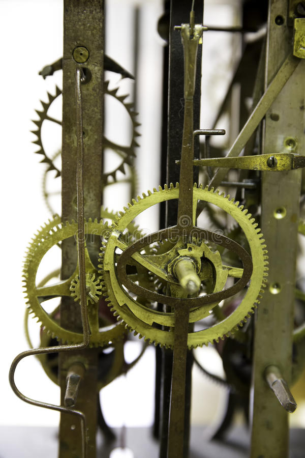 Close up view of greasy and rusty old wall clock mechanism with gears. Isolated on white background royalty free stock image