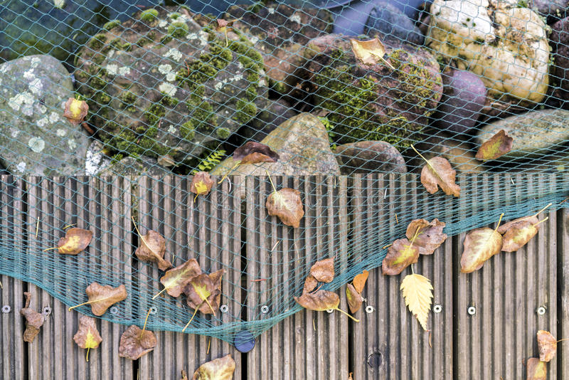 Close up view of green netting over large rocks stock photo