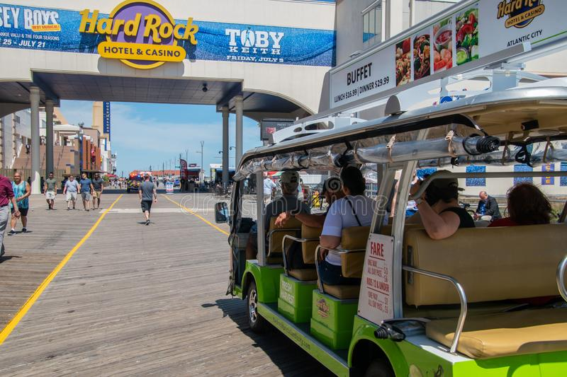 Close up view of a green Tram car filled with tourists riding on the Atlantic City Boardwalk near the Hard Rock Hotel sign stock photography