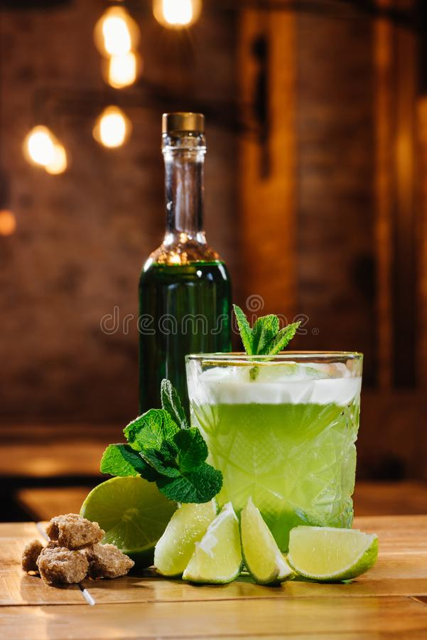 Close-up view of green van gogh cocktail in glass with bottle of absinthe. On wooden table royalty free stock images