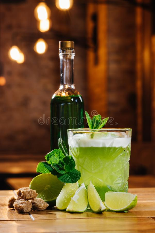 Close-up view of green van gogh cocktail in glass with bottle of absinthe on wooden table royalty free stock image