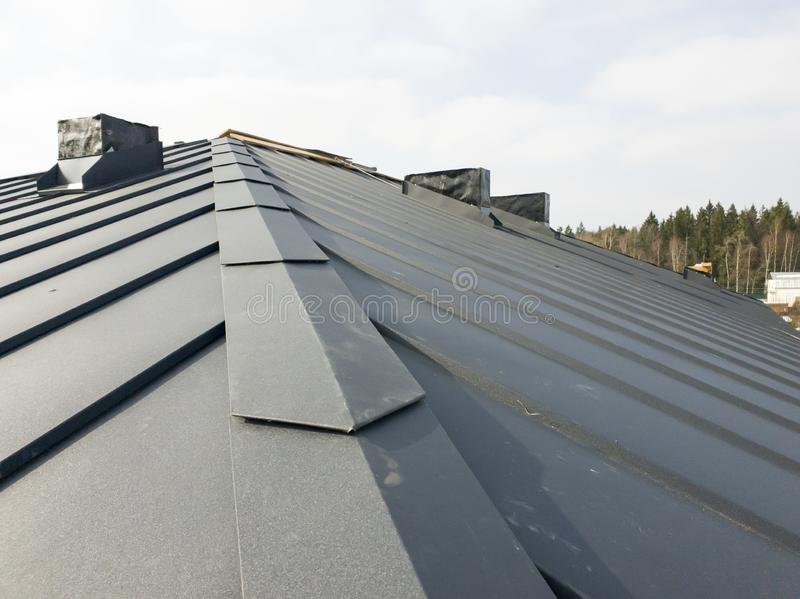 Close up view of grey folding roof and chimney on waterproofing layer of house under construction. Metal, , , sheet, folded, building, gray, industry royalty free stock image
