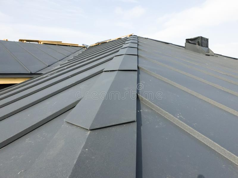Close up view of grey folding roof and chimney on waterproofing layer of house under construction. Metal, , corrugated, sheet, folded, building, gray, industry stock photo