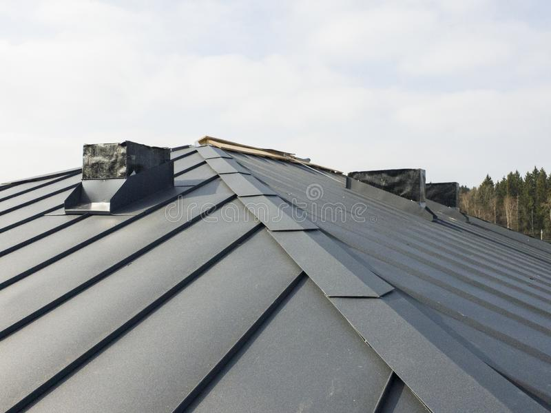 Close up view of grey folding roof and chimney on waterproofing layer of house under construction. Metal, steel, corrugated, sheet, folded, building, gray royalty free stock photo