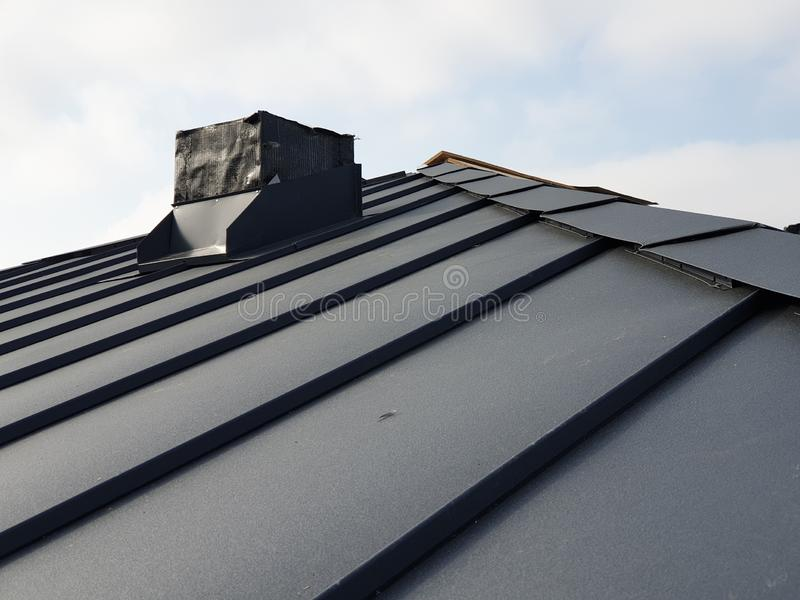Close up view of grey folding roof and chimney on waterproofing layer of house under construction. Steel, , sheet, folded, building, gray, industry royalty free stock images