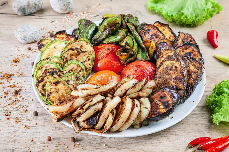 Close up view on grilled vegetables on white plate served on white wooden table. tomato, pepper, eggplant, zucchini and onion royalty free stock photography