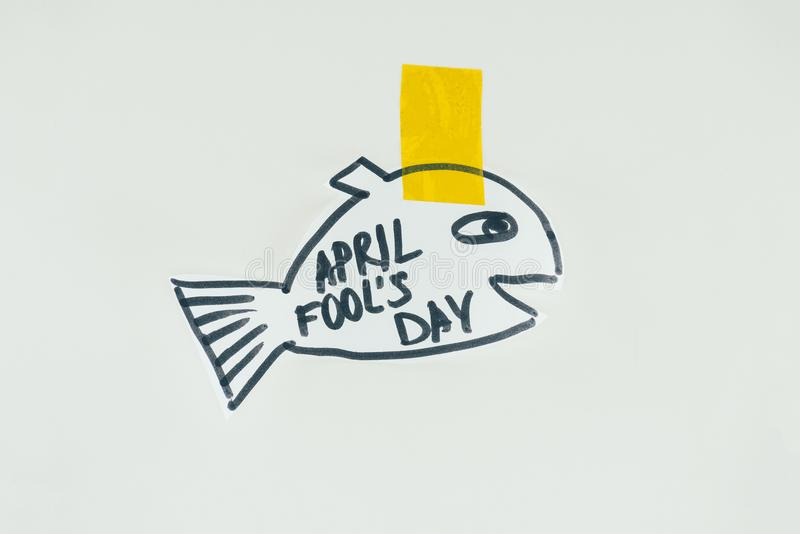Close up view of hand drawn fish with april fools day lettering and sticky tape isolated on grey, april fools day holiday concept stock photography