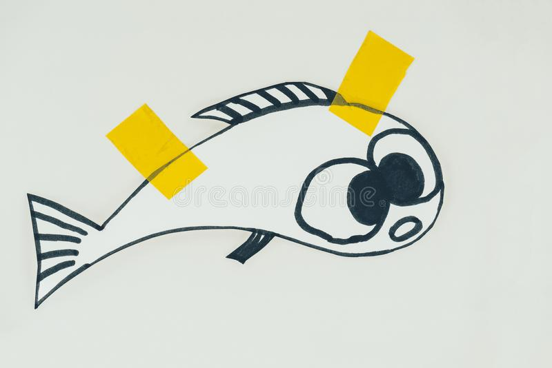 Close up view of hand drawn fish with sticky tapes isolated on grey, april fools day holiday concept royalty free stock photography