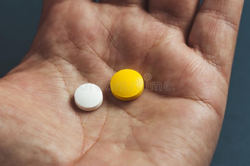 close-up view of a hand holding two pills stock photography