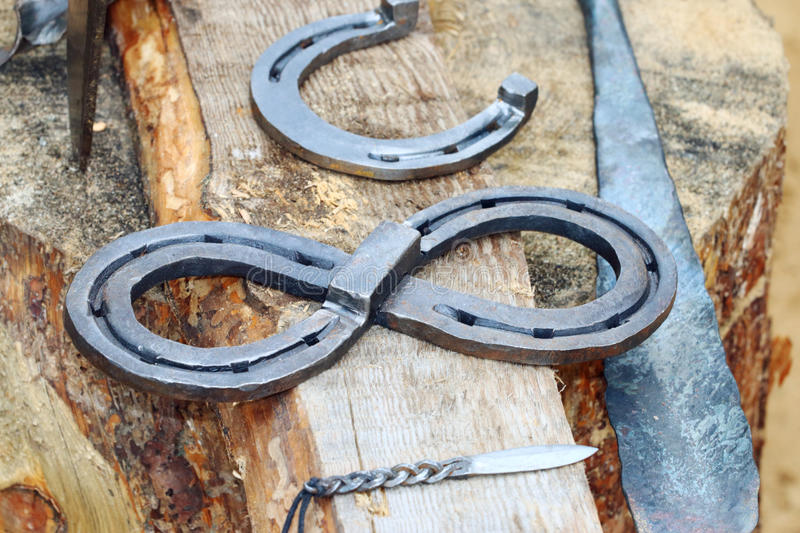Close up view of handicrafts knife, horseshoe on wooden stump royalty free stock photos