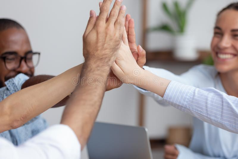Close up view happy diverse business team giving high five stock image