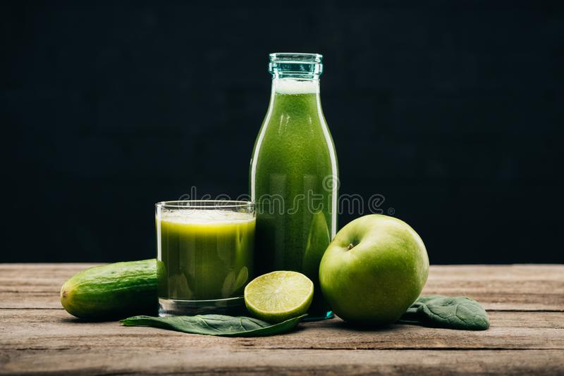 Fresh food and detox drink. Close up view of healthy fresh food and detox drink on wooden tabletop isolated on black royalty free stock photos