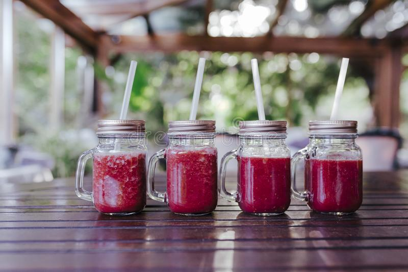 close up view of for healthy juice in small jars on the table. Made of watermelon, orange and blackberries. Home made, healthy stock photo