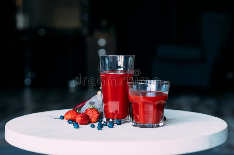 Close-up view of healthy natural red smoothie in glasses and organic ingredients. On table royalty free stock photo