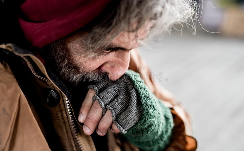 A close-up view of homeless beggar man standing outdoors in city. stock images