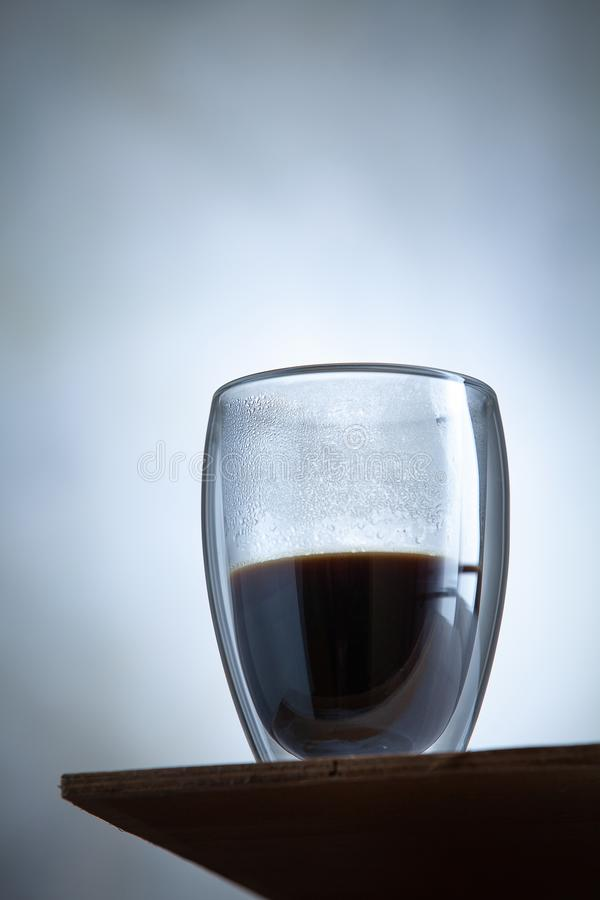 Close up view on hot glass of coffe stands in front of a concrete wall. Morning drink cocnept. Breakfast, Creaitive still life. Photo of food. trending double stock image