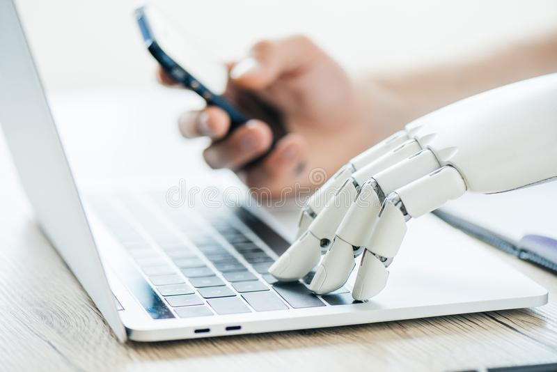 Close-up view of human and robot hands using smartphone and laptop. At wooden table royalty free stock photos