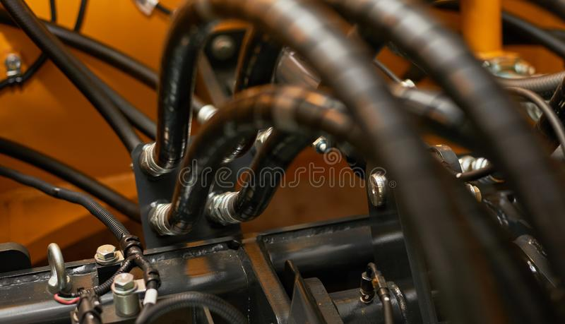 Close up view of hydraulic pipes of heavy industry machine. Low key royalty free stock photo