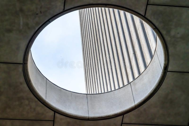 Close up view from the inside of the round skylight of a building. Corrugated concrete wall and bright sky can be seen through the hole stock images