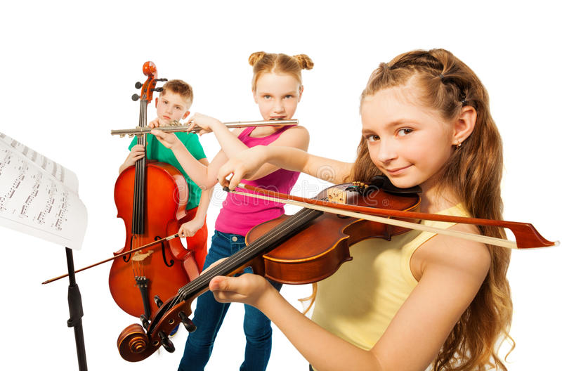Close-up view of kids playing musical instruments. Close-up view of cute kids playing on musical instruments together on white background stock photo