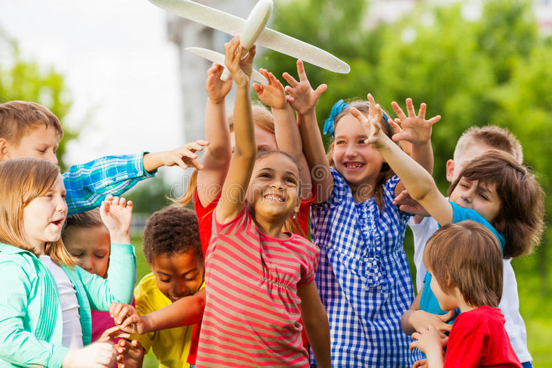 Close-up view of kids reaching after airplane toy. Close-up view of kids reaching after big white airplane toy with arms standing close in the field during stock image