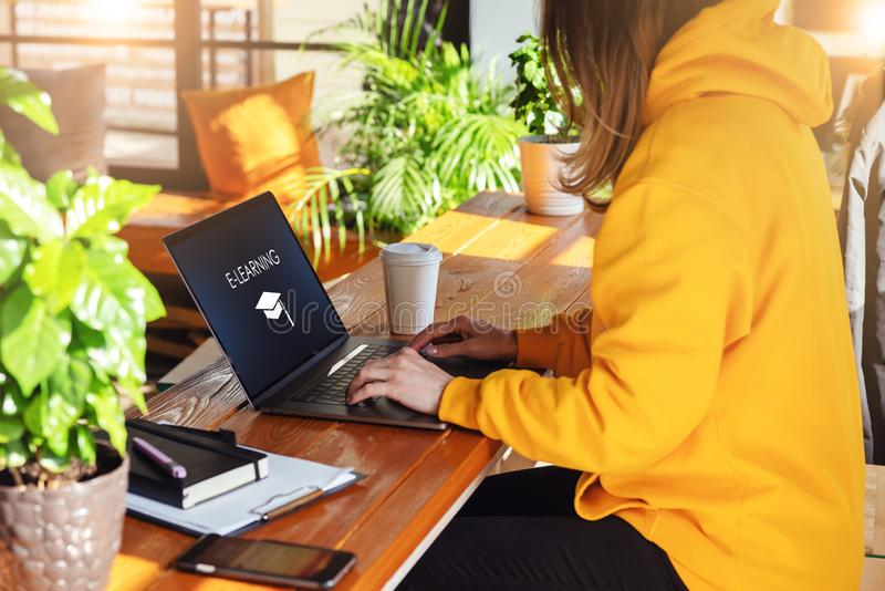 Close-up view of laptop screen with inscription e-learning.Girl in yellow hoodie works on computer in cafe. Education stock images
