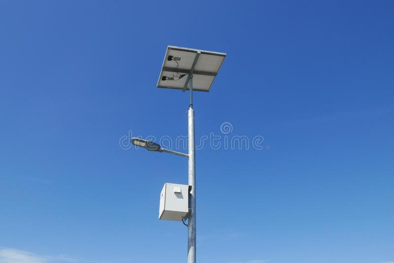 Close up view of LED street light with solar cell on clear blue sky background with clouds. stock photo