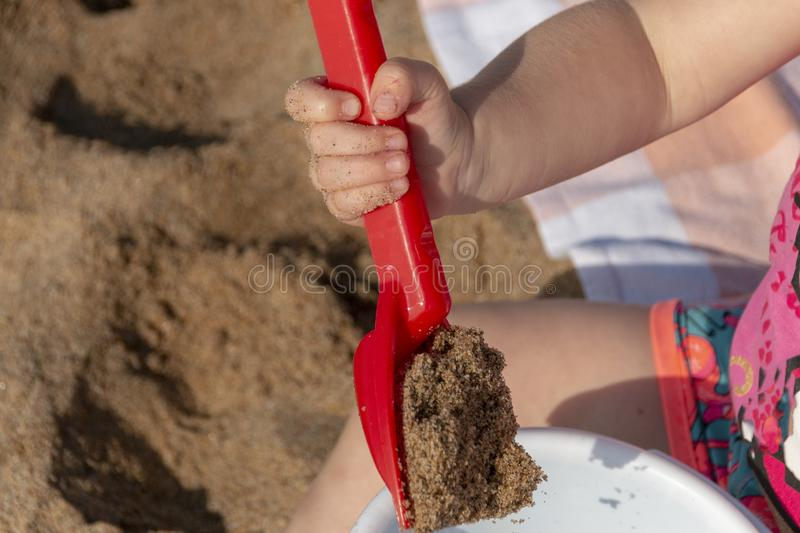 A Little girls hands. A close up view of a little girls hand with her spade and bucket playing with the beach sand on a beautiful summers day royalty free stock image