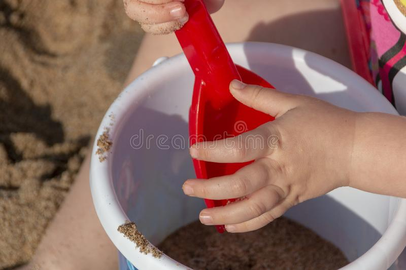 A Little girls hands. A close up view of a little girls hand with her spade and bucket playing with the beach sand on a beautiful summers day stock image