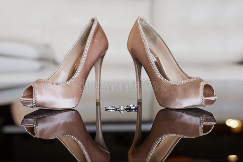 Close up view of luxury platinum wedding rings with diamonds and female wedding shoes before the wedding ceremony royalty free stock images