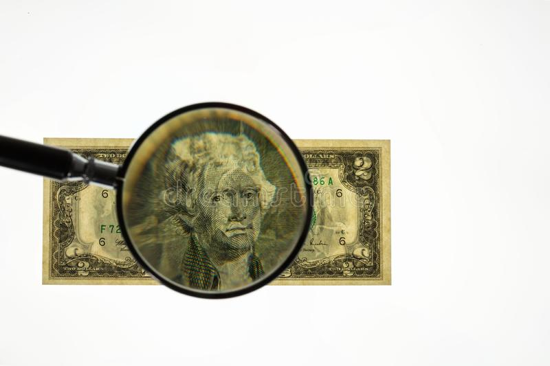 Close up view of magnifying glass over two dollar bill. Banknote. royalty free stock photo