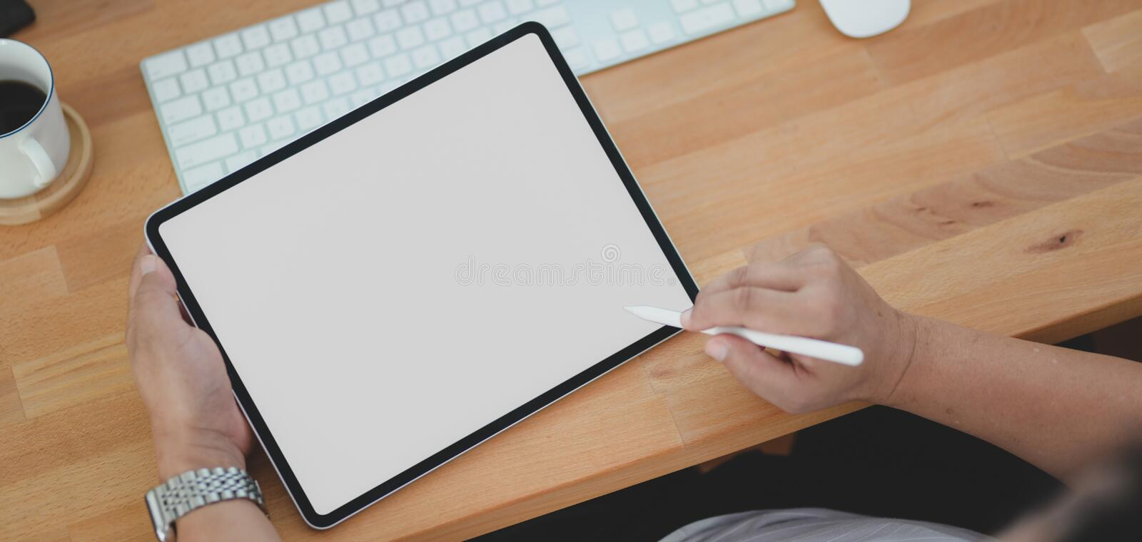 Close-up view of male freelancer working on his project with blank screen tablet. In his comfortable room stock photos