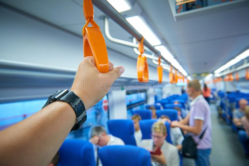 Close up view on man hand holding the handle of train handrail and blured train interior and passengers in the background royalty free stock photography