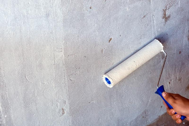 Close up view of man hand paint gray concrete ceiling with paint roller. Interior decoration concept stock image