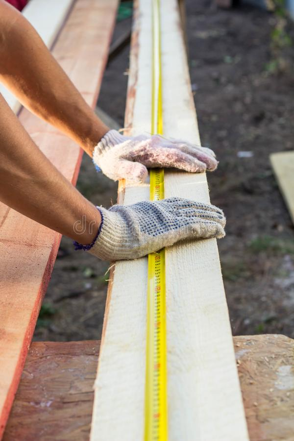 Close up view of a man hands measuring wooden plank with a tape line royalty free stock images