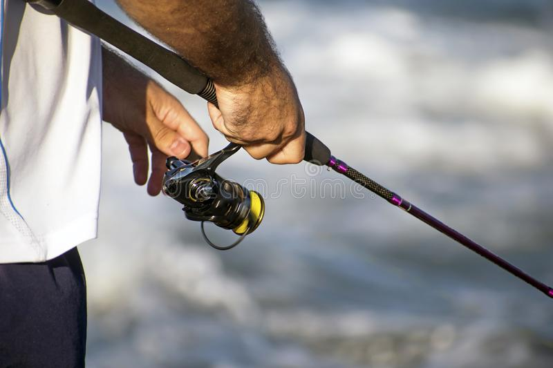 Unidentified man reeling in after hooking a fish. Close up view man holding a reel and fishing against sea tackle selective aqua camping spin rods serene pole stock image