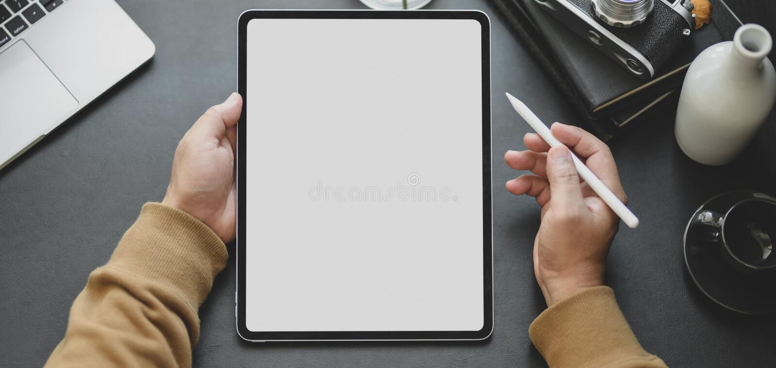 Close-up view of man using blank screen tablet while working in dark modern workplace. Close-up view of man using blank screen tablet while working in his dark royalty free stock photography
