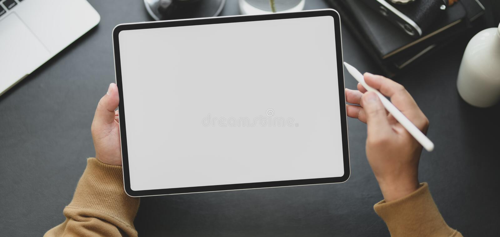 Close-up view of man using blank screen tablet while working in dark modern workplace. Close-up view of man using blank screen tablet while working in his dark stock photo