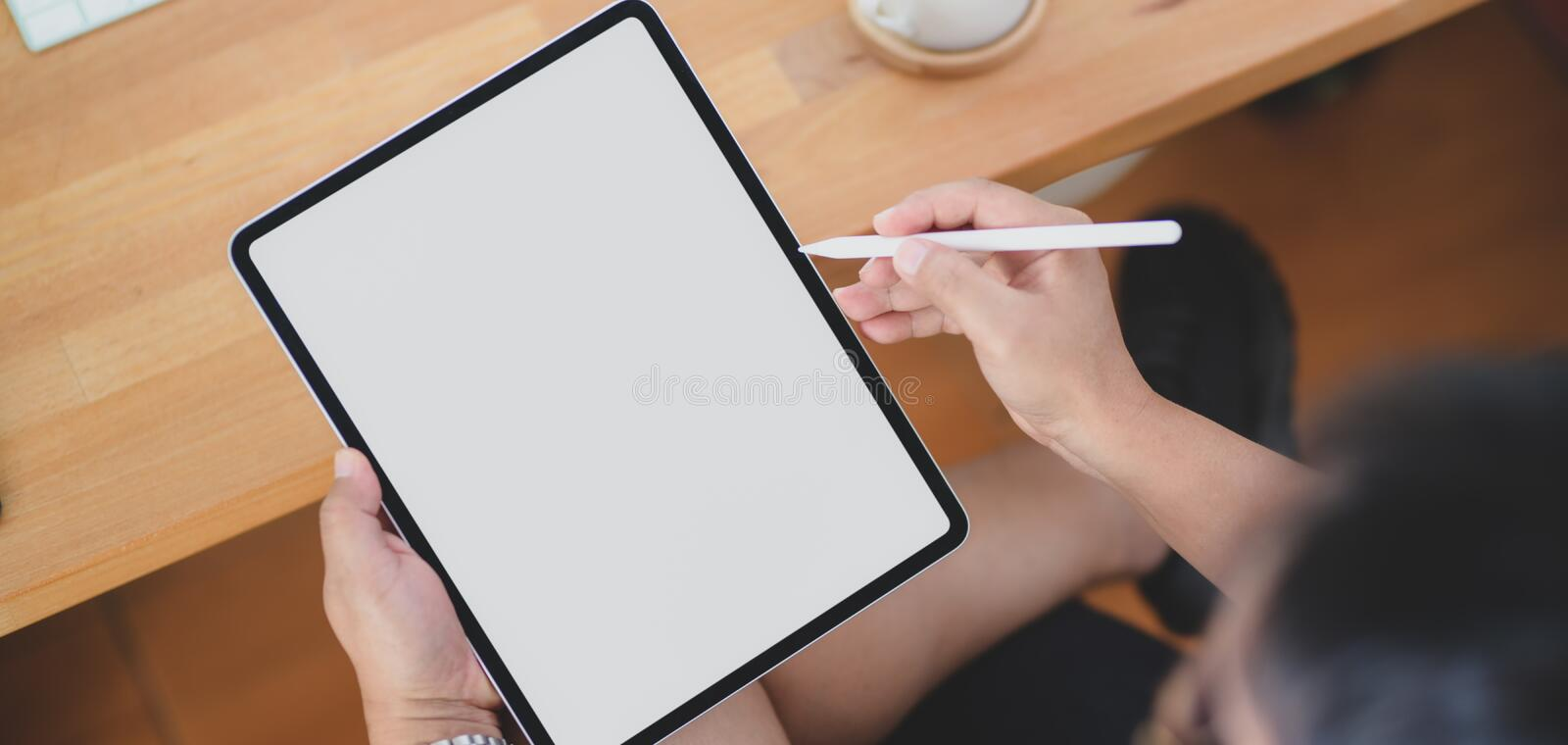 Close-up view of man working on his project with blank screen tablet. In his comfortable room royalty free stock photography