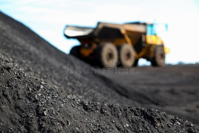 Close up view of Manganese ore with Mining Dump Truck in the background. Close up view of Manganese ore powder with Mining Dump Truck in the background stock photo