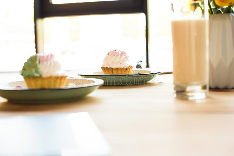 Close-up view of milkshake in glass and delicious cupcakes on plates. In cafe stock photo