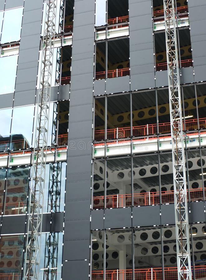 Close up view of a modern construction site with hoists running up the tall building with steel girders with black panels and wind stock photography